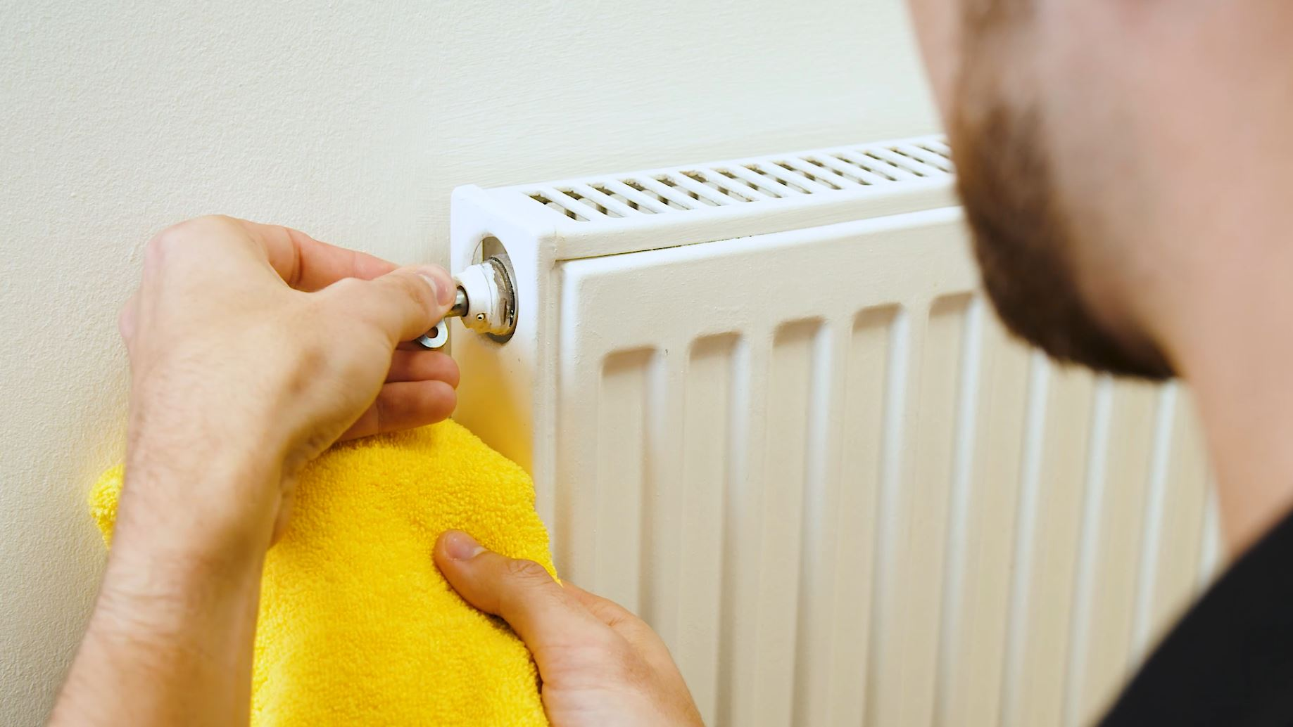 man holding radiator key next to radiator